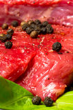 Raw beef steak. With black pepper on the leaf of lettuce Royalty Free Stock Photos