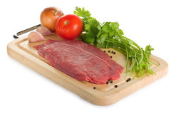 Raw beef steak. On a cutting board isolated on white background Royalty Free Stock Images