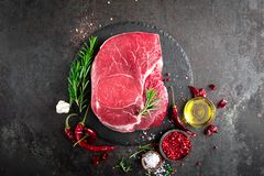 Raw beef steak on black background with cooking ingredients. Fresh beef meat. Top view Royalty Free Stock Images