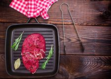 Raw beef steak on a black quart pan Royalty Free Stock Photos
