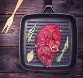 Raw beef steak on a black quart pan. Top view Stock Images