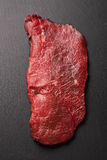 Raw beef steak on black stone Royalty Free Stock Photography