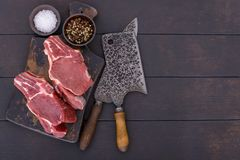 Raw beef steak with bone on wooden board. And table with copy space Stock Photography