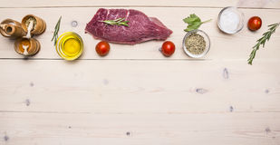 Raw beef steak with butter and spices, laid out around it,  border ,place for text  wooden rustic background top view close up Royalty Free Stock Images