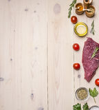 Raw beef steak with butter and spices, laid out around it,  border ,place for text  wooden rustic background top view close up Stock Photos