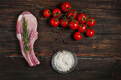 Raw beef steak and cherry tomatoes on a dark wooden table Royalty Free Stock Photo