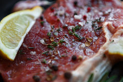 Raw beef steak closeup background with spices and herbs. Raw beef steak closeup, selective focus. Fresh juicy meat marinated with herbs and spices, rosemary and Royalty Free Stock Image