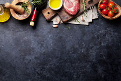 Raw beef steak cooking. And ingredients. Meat piece, red wine, herbs and spices. Top view with copy space over stone table Royalty Free Stock Image