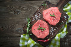 Raw beef steak on a cutting board. Raw meat. Raw beef steak on a cutting board with herbs and spices. Top view with copy space Royalty Free Stock Images