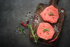 Raw beef steak on a cutting board. Raw meat. Raw beef steak on a cutting board with herbs and spices. Top view with copy space Royalty Free Stock Image