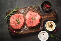 Raw beef steak on a cutting board. Raw meat. Raw beef steak on a cutting board with herbs and spices. Top view with copy space Royalty Free Stock Photo