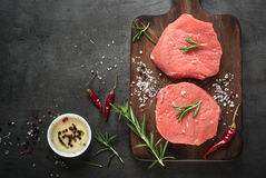 Raw beef steak on a cutting board. Raw meat. Raw beef steak on a cutting board with herbs and spices. Top view with copy space Stock Photos