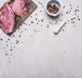 Raw beef steak on a cutting board with pepper border ,place for text  wooden rustic background top view close up. Raw beef steak on a cutting board with pepper Royalty Free Stock Photos