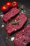 Raw beef steak on a cutting board with rosemary and cherry tomatoes. Raw meat. Raw beef steak on a cutting board with rosemary and cherry tomatoes Stock Photos