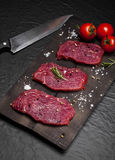 Raw beef steak on a cutting board with rosemary and cherry tomatoes. Raw meat. Raw beef steak on a cutting board with rosemary and cherry tomatoes Royalty Free Stock Images