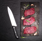 Raw beef steak on a cutting board with rosemary and cherry tomatoes. Raw meat. Raw beef steak on a cutting board with rosemary and cherry tomatoes Stock Images