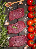 Raw beef steak on a cutting board with rosemary and cherry tomatoes. Raw meat. Raw beef steak on a cutting board with rosemary and cherry tomatoes Stock Image