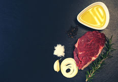 Raw beef steak on a cutting board. With rosemary and spices Stock Photo