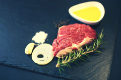 Raw beef steak on a cutting board. With rosemary and spices Stock Image
