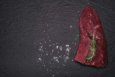 Raw beef steak on a cutting board with rosemary and spices. Stock Images