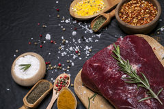 Raw beef steak on a cutting board with rosemary and spices. Raw meat. Raw beef steak on a cutting board with rosemary and spices Stock Images