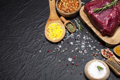 Raw beef steak on a cutting board with rosemary and spices. Raw meat. Raw beef steak on a cutting board with rosemary and spices Royalty Free Stock Photos