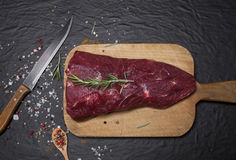 Raw beef steak on a cutting board with rosemary and spices. Raw meat. Raw beef steak on a cutting board with rosemary and spices Stock Photo