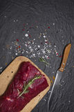 Raw beef steak on a cutting board with rosemary and spices. Raw meat. Raw beef steak on a cutting board with rosemary and spices Royalty Free Stock Images