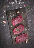 Raw beef steak on a cutting board with rosemary and spices. Raw meat. Raw beef steak on a cutting board with rosemary and spices Royalty Free Stock Image