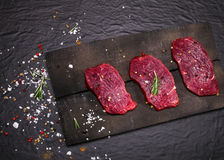 Raw beef steak on a cutting board with rosemary and spices. Raw meat. Raw beef steak on a cutting board with rosemary and spices Stock Photos