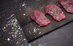 Raw beef steak on a cutting board with rosemary and spices. Raw meat. Raw beef steak on a cutting board with rosemary and spices Royalty Free Stock Photography