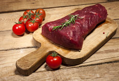 Raw beef steak on a cutting board with rosemary and spices. Raw meat. Raw beef steak on a cutting board with herbs, spices and cherry tomatoes Stock Images