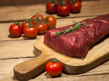 Raw beef steak on a cutting board with rosemary and spices. Raw meat. Raw beef steak on a cutting board with herbs, spices and cherry tomatoes Stock Image