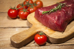 Raw beef steak on a cutting board with rosemary and spices. Raw meat. Raw beef steak on a cutting board with herbs, spices and cherry tomatoes Royalty Free Stock Images