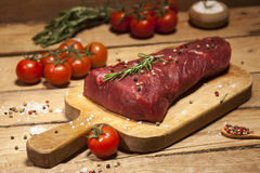 Raw beef steak on a cutting board with rosemary and spices. Raw meat. Raw beef steak on a cutting board with herbs, spices and cherry tomatoes Royalty Free Stock Photography