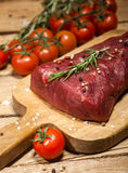 Raw beef steak on a cutting board with rosemary and spices. Raw meat. Raw beef steak on a cutting board with herbs, spices and cherry tomatoes Royalty Free Stock Photos