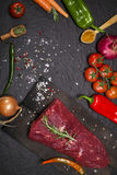 Raw beef steak on a cutting board with rosemary and spices. Stock Photo