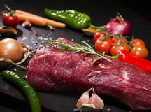 Raw beef steak on a cutting board with rosemary and spices. Stock Photography