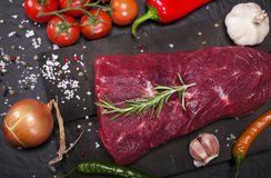 Raw beef steak on a cutting board with rosemary and spices. Royalty Free Stock Photography