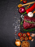 Raw beef steak on a cutting board with rosemary and spices. Royalty Free Stock Image