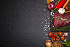 Raw beef steak on a cutting board with rosemary and spices. Royalty Free Stock Photo