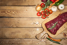 Raw beef steak on a cutting board with rosemary and spices. Stock Image