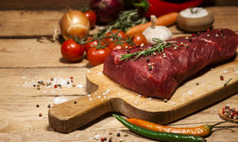 Raw beef steak on a cutting board with rosemary and spices. Stock Photos