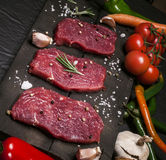 Raw beef steak on a cutting board with rosemary and spices. Royalty Free Stock Photos