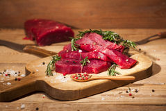 Raw beef steak on a cutting board with rosemary and spices. Raw meat. Raw beef steak on a cutting board with rosemary and spices on wooden background Stock Photo