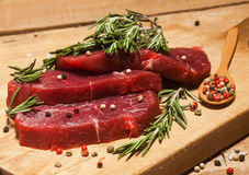 Raw beef steak on a cutting board with rosemary and spices. Raw meat. Raw beef steak on a cutting board with rosemary and spices on wooden background Royalty Free Stock Photography