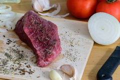 Raw beef steak on a cutting board with spices ready for cooking. Raw beef steak on a cutting board with spices and vegetable Stock Images
