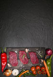 Raw beef steak on a cutting board with vegetables and spices. Stock Photos