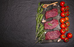 Raw beef steak on a cutting board with vegetables and spices. Royalty Free Stock Photos