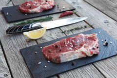 Raw beef steak on dark wooden table background. Fresh juicy meat on black stone cutting desk, knife and lemon slice. Cooking ingredients, butcher`s and grocery Royalty Free Stock Images